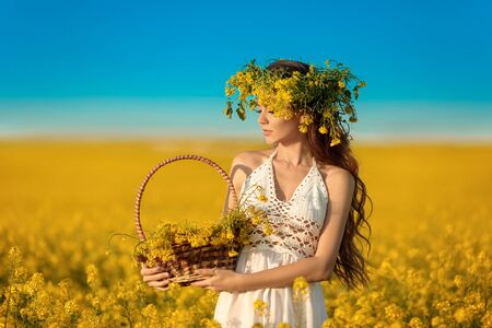 Beautiful young woman with wreath on long healthy hair over Yellow rape field landscape background. Attracive brunette girl with curly hairstyle holding basket with flowers, outdoor portrait. Stok Fotoğraf