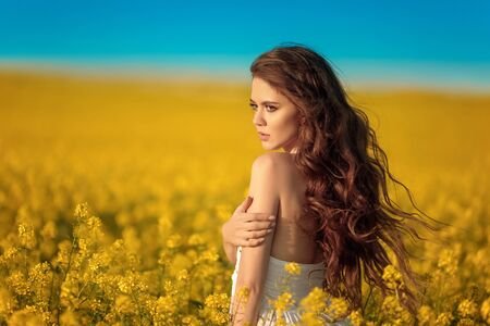 Beautiful carefree girl with long curly healthy hair over Yellow rape field landscape background. Attracive brunette with blowing hairstyle enjoying sunset, outdoor beauty portrait.