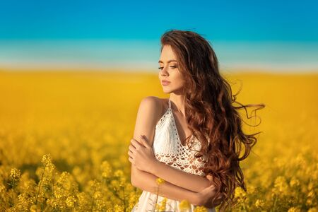 Beautiful carefree girl with long curly healthy hair over Yellow rape field landscape background. Attracive brunette with blowing hairstyle enjoying and breathing sunset, outdoor beauty portrait. Zdjęcie Seryjne