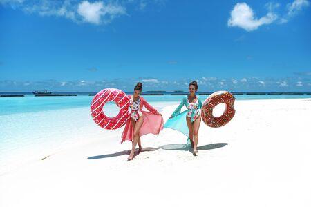 Summer Vacation. Happy free two women with Inflatable donut float mattress. Girls wearing Chiffon Beach Dress enjoying exotic beach by turquoise water seaside. Maldives island paradise background. Reklamní fotografie