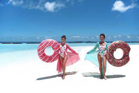 Summer Vacation. Happy free two women with Inflatable donut float mattress. Girls wearing Chiffon Beach Dress enjoying exotic beach by turquoise water seaside. Maldives island paradise background.