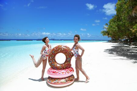 Summer Vacation. Happy free two women with Inflatable donut float mattress. Girls in fashion swimwear  having fun and enjoying exotic beach by turquoise water. Maldives island paradise background.