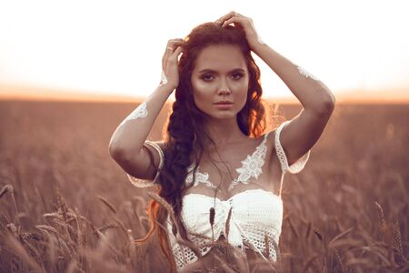 Boho style portrait of bohemian girl with white art posing over wheat field at sunset. Outdoors photo. Tranquility concept.