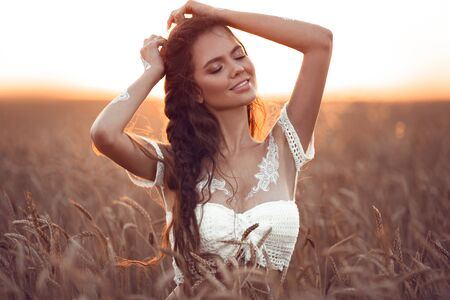 Boho chic style. Portrait of bohemian girl with white art posing over wheat field enjoying at sunset. Outdoors photo. Tranquility concept. Lifestyle.
