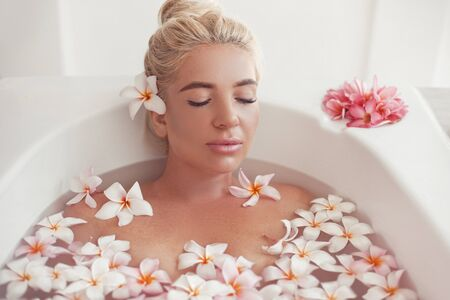Spa Relax. Blonde enjoying bath with plumeria tropical flowers. Health And Beauty. Closeup Beautiful Sexy Girl Bathing With Petals. Treatment, Aromatherapy Skin Body Care Therapy.