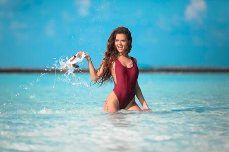 Sexy model on Beach vacation. Happy fun girl holding snorkel scuba mask standing in ocean water. Maldives summer. Young woman enjoying life. Zdjęcie Seryjne
