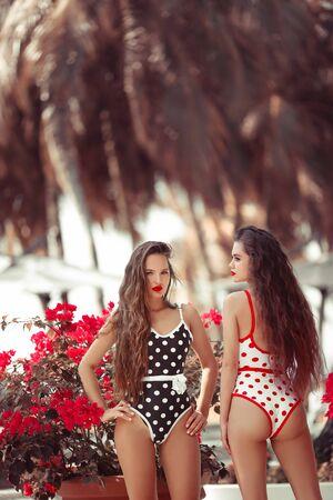 Sexy Pinup girls with red lipstick makeup posing in trendy bikini. Summer lifestyle fashion portrait of two brunette women. Enjoying life. Wearing stylish pin up polka dot swinwears. Zdjęcie Seryjne