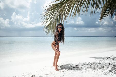 Bikini Model posing on white sand by palm. Brunette on tropical beach vacation. Sexy slim girl in black swimwear. Maldives Summer. 写真素材 - 132460045