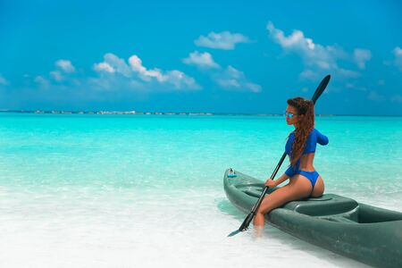 Sexy brunette paddling a kayak. Fashion Woman in blue bikini exploring calm tropical bay. Maldives island. Sporty activity. Summer water sport, adventure outdoors. 版權商用圖片