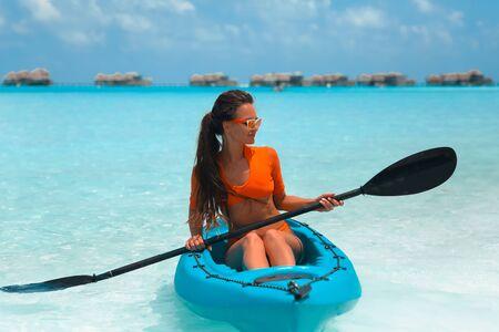Sexy brunette paddling a kayak. Woman exploring calm tropical bay. Maldives. Sport, recreation. Summer water sport, adventure outdoors.