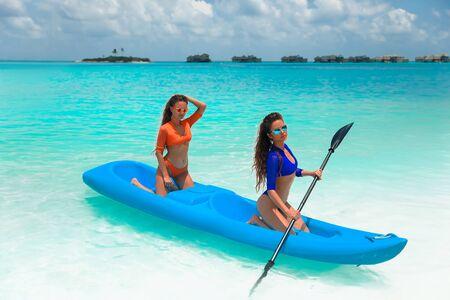 Two sexy bikini models in swimwear posing on kayak, on tropical beach paradise island. Maldives paradise. Summer water sport, adventure outdoors. Joyful young women kayaking together.