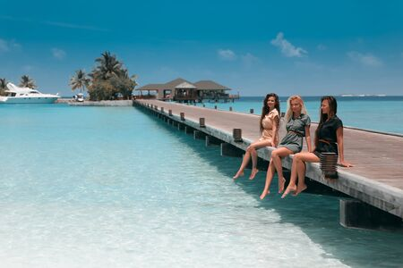 Three girls sitting on wooden planks on tropical beach Maldives. Girlfriends  having fun, pleasure and enjoyment. Slim cute models with healthy long hair at Summer vacations.