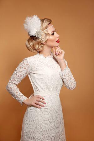 Elegant lady in wedding white dress with retro hairstyle posing isolated on studio beige background. Beautiful blonde bride woman. Vintage style photo.