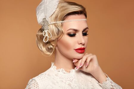 Portrait of Retro woman with red lips and wavy hairstyle, feather in head. Elegant lady in wedding white dress posing isolated on studio beige background. Beautiful blonde bride.