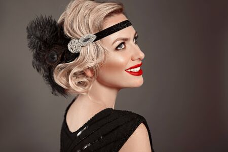 Retro woman portrait. Blonde wavy hairstyle. Hollywood red lips makeup. Curly hair style. Beautiful elegant female wears in vintage dress isolated on dark studio background. Stock fotó