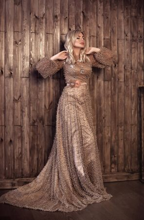Elegant blond woman in beige pearls dress posing against wooden wall background with copy space area. Fashion beautiful sensual female with makeup, curly hair style in long prom gown.