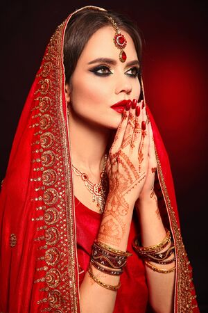 Portrait of beautiful indian girl in red bridal sari. Young hindu woman model with kundan jewelry set. Traditional Indian costume lehenga choli. Henna painting, mehendi on bride's hands.