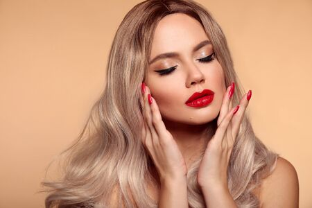 Makeup, manicured nails. Beauty portrait of blonde woman with red lips, long healthy shiny blond hair style. Sensual girl with bright makeup isolated on beige backhround. 免版税图像