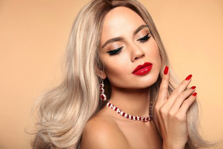 Ruby jewelry. Beauty portrait of blonde woman with red lips makeup and manicured nails. Sensual girl with long healthy shiny blond hair style isolated on beige studio backhround.