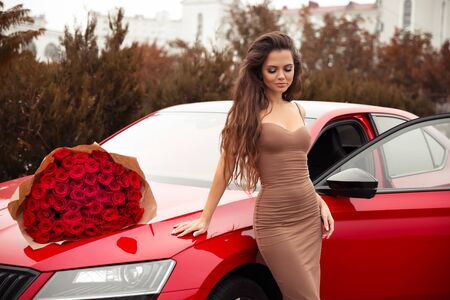 Beautiful sexy woman with rose bouquet of flowers on bonnet posing by new red car. Beauty outdoor autumn portrait. Brunette in beige slim dress. Valentines day. Romantic expensive luxury gift. 免版税图像