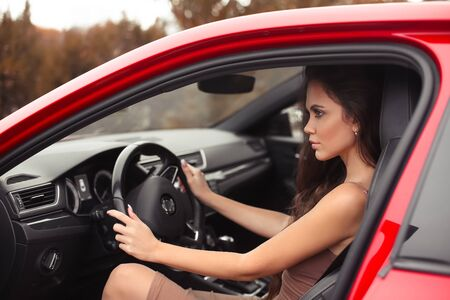 Closeup portrait of attractive young woman profile in casual wear looking on road while driving a red car. Confident and beautiful. 免版税图像