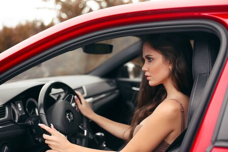Closeup portrait of attractive young woman profile in dress looking on road while driving a red car. Confident and beautiful. Auto concept.
