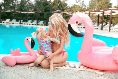 Family look. Beautiful mother having fun with daughter. Happy summer vacations.  Blonde pretty woman with her little girl wear in fashion same swimwears playing by pink Inflatable pool float flamingo. 免版税图像