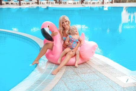 Happy family look. Mother with daughter. Beautiful blond woman with having fun with little pretty gil wears in swim wear posing on Inflatable Flamingo Pool Float by swimming pool.