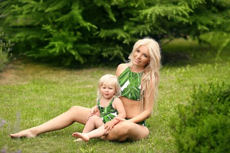 Beauty family look. Beautiful mother with daughter relax on green grass at park.  Glamour blonde woman having fun with pretty little girl wears in same fashion swimwears. Summer resort vacation.