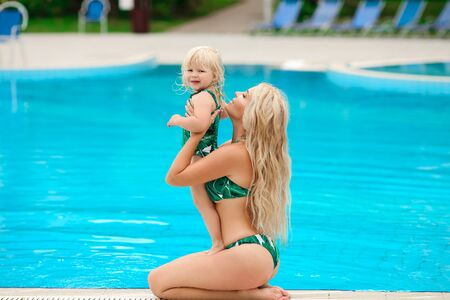 Family look, swimwear outfit. Beautiful blond mother with her pretty daughter having fun and relaxed by swimming pool on villa beach. Happy Summer time vacations.
