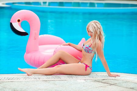 Fashion sexy blond model woman in white bikini posing on Pink inflatable flamingo by swimming pool ring, tube, float. Summer vacation holiday luxurious resort.