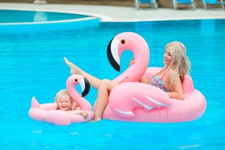 Happy family look summer vacations. Beautiful mother having fun with daughter.  Blonde pretty woman with her little girl wears in fashion same swimwears relax on pink Inflatable pool float flamingo.