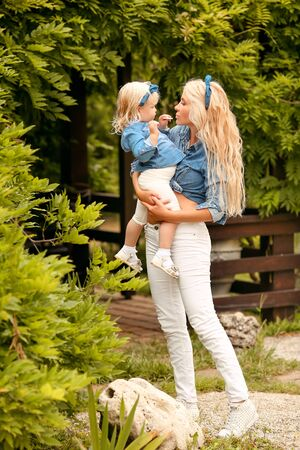 Family look. Blonde Mother and daughter holding and playing on summer park. Happy family lifestyle concept. Beautiful portrait of Mom and her pretty girl in same clothes.