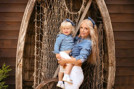 Happy family lifestyle concept. Family look. Portrait of Blonde Mother holding her daughter hugging by boat with fishing net. Beautiful woman and her pretty girl wear same clothes.