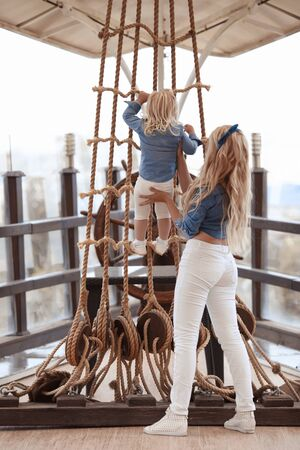 Beauty fashion mother with daughter family look. Beautiful blond woman playing with her little pretty blonde girl climb a rope by wooden ship's wheel helm. 免版税图像