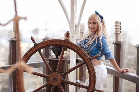 Beautiful blonde woman portrait wears fashion outfit clothes style posing with ship rope by wheel helm. 免版税图像