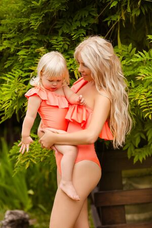 Family look. Beautiful Mother holding her little blonde daughter over green park, on Summer vacations. Pretty girls wears in fashion orange swimwear having fun. Parenthood outdoor portrait.