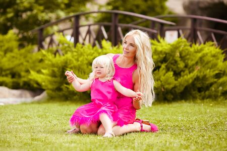 Family look. Beautiful blonde mother with her daughter in pink dresses playing on green grass at spring park. Happy fun same girls. Lifestyle concept.