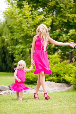 Beautiful mother with her daughter wear pink dresses walking in green spring park. Happy Family fun. Lifestyle concept.