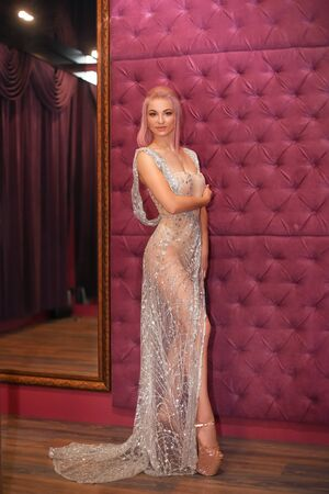 Beautiful woman in shining beige glitter dress posing by velvet capitone wall in strip night club. Poledance. Glamour poledancer girl.