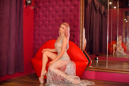 Beautiful woman in shining beige glitter dress sitting on red lips sofa by velvet capitone wall in strip night club. Poledance. Glamour poledancer girl. 免版税图像