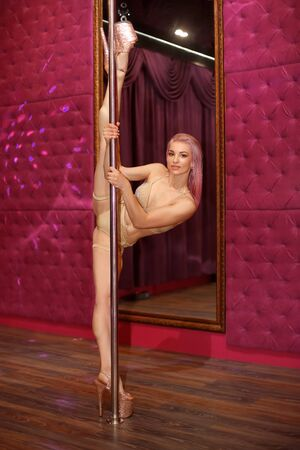 Sexy woman pole doing gymnastic split in studio of poldance. Striptease girl  in high heels shoes doing stretching in strip night club. 免版税图像