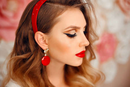 Beauty Portrait of girl with perfect makeup and red jewelry. Beautiful model woman with long curly hairstyle. Eyelashes. Cosmetic eyeshadow. Care and beauty face products.
