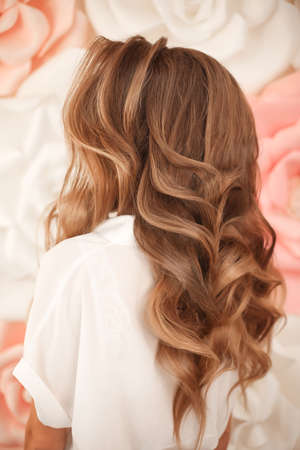 Healthy hair. Wavy long hairstyle. Back view of Blond hair styling. Wedding day. Bride High Fashion Coiffure. Close up of hairdo