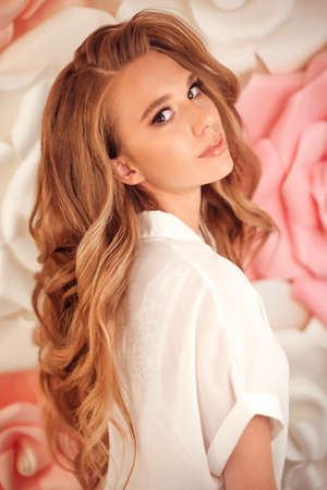 Beauty Makeup. Red hair girl model with long wavy hairstyle and shiny eyeshadows. Portrait of young attractive caucasian woman posing over flowers wall.