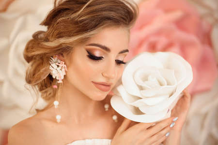 Beautiful young bride with makeup and fashion wedding hairstyle. Closeup portrait of young gorgeous woman over roses flowers. Studio shot.