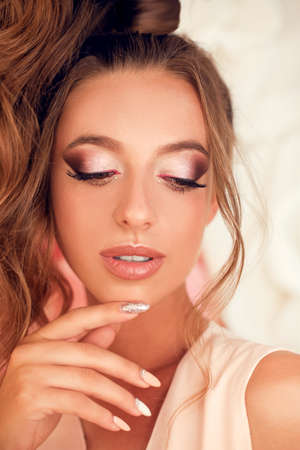 Woman face Make-up portrait. Manicure nails. Beauty fashion model girl pink eyeshadows makeup, tone skin, glossy lipstick and curly hair style.