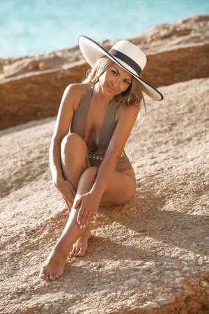 Fashion outdoor portrait of sensual bikini model in white hat. Carefree Woman Enjoying Beautiful Sunset on the Beach.
