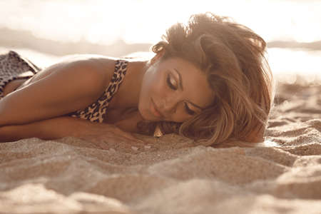 Fashion outdoor portrait of sensual bikini model. Carefree Woman Enjoying Beautiful Sunset on the sandy Beach. Golden makeup.