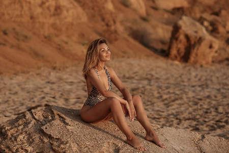 Carefree Woman Enjoying Beautiful Sunset on the Beach. Fashion outdoor photo of sensual bikini model. Zdjęcie Seryjne